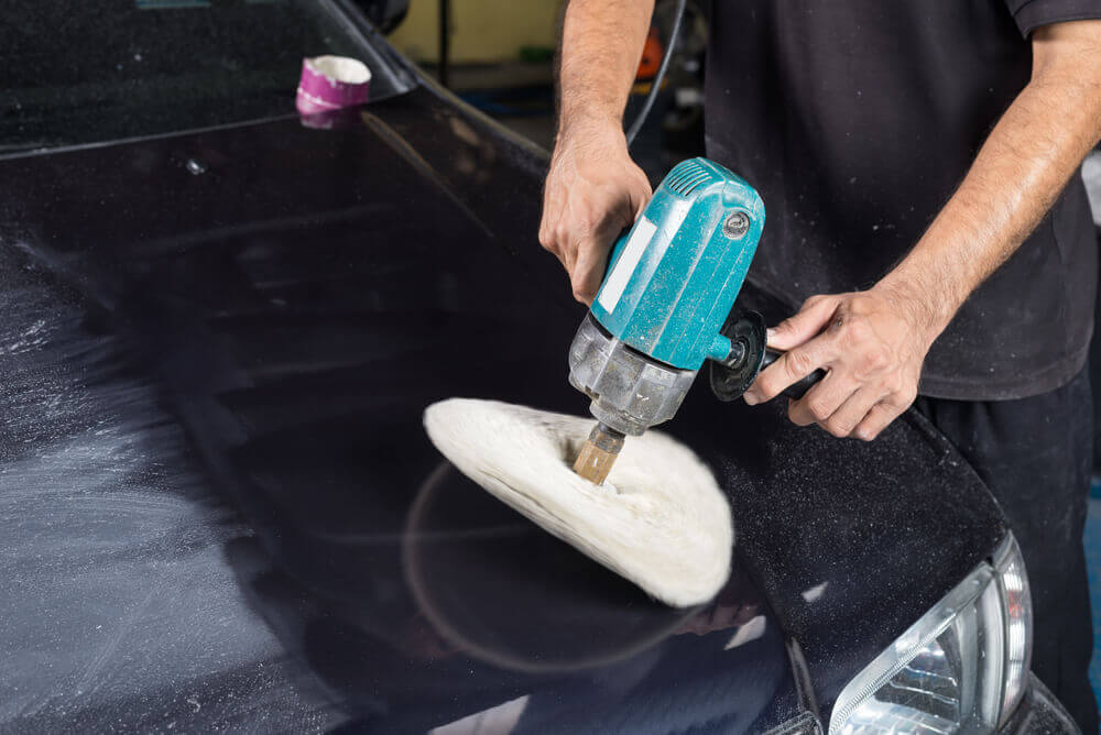 a car detailing worker using a wool polishing machine to clean the bonnet of a black car