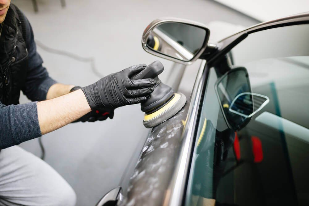 a worker polishing the side of a car with an electric buffer