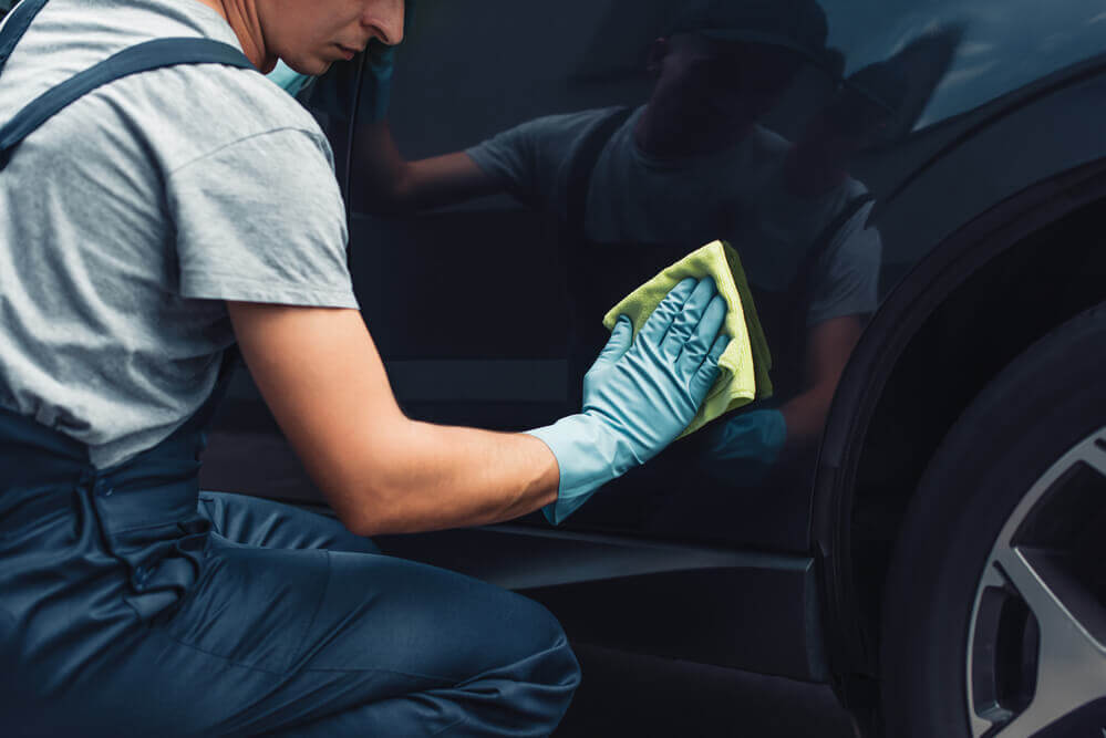 a detailer wiping down the rear door of a clean car with a microfiber cloth